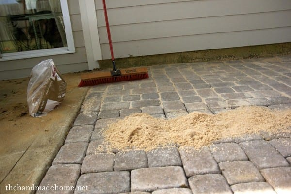 Once level, pour out a bag or two of sand over the patio. Use a stiff  bristle brush push broom, and spread the sand all over the patio. - Backyard Bliss: Installing Patio Pavers And A Fire Pit {diy Patio